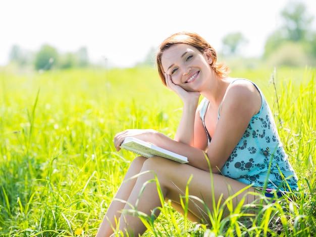 かなり笑顔の女性が自然の中で本を読む