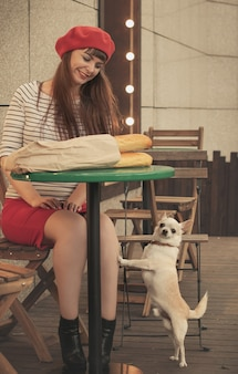 Pretty smiling woman in red beret sits at table in cafe with baguette in paper bag