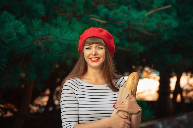 Pretty smiling woman in red beret and striped jacket holds paper bag with baguette