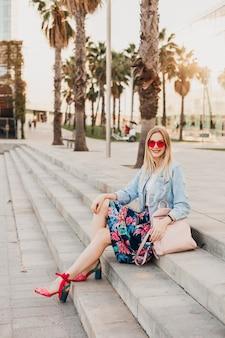スタイリッシュなプリントスカートとデニムのオーバーサイズジャケットのピンクのサングラス、夏のスタイルのトレンドを身に着けている革のバックパックで街の階段に座っているかなり笑顔の女性