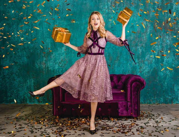 Pretty smiling woman in stylish violet evening dress against velvet sofa with gifts