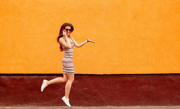 Pretty smiling woman in sunglasses talking on the smartphone against the orange wall