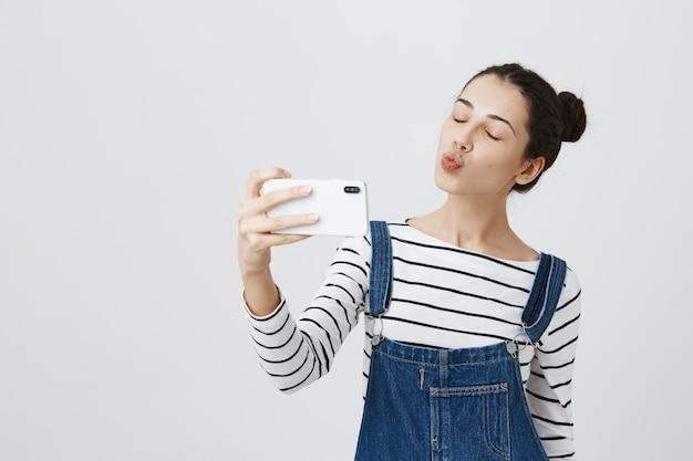かなり笑顔の女性がスマートフォンでselfieを取って、キスのためにふくれっ面