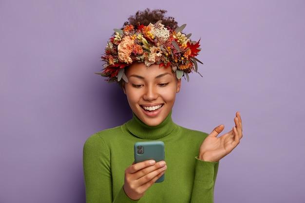 예쁜 웃는 여자는 휴대 전화를 사용하고 손바닥을 들고 긍정적으로 웃음을 짓고 상징적 인 가을 화환과 녹색 점퍼를 착용합니다.