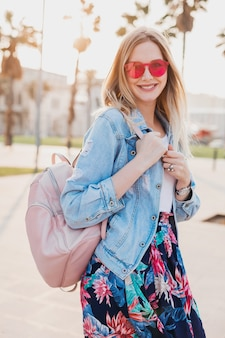 Donna abbastanza sorridente che cammina nella strada della città in elegante gonna stampata e giacca oversize in denim che indossa occhiali da sole rosa, che tiene zaino in pelle, tendenza stile estivo