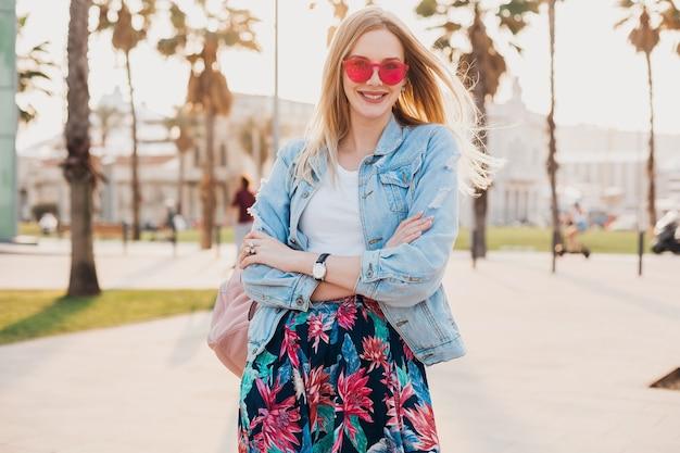 Donna abbastanza sorridente che cammina nella strada della città in elegante gonna stampata e giacca oversize in denim indossando occhiali da sole rosa, tendenza stile estivo
