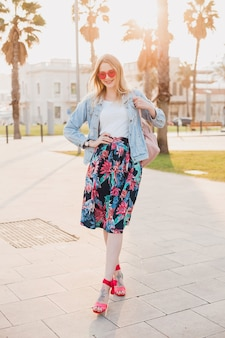 Pretty smiling woman walking in city street in stylish printed skirt and denim oversize jacket wearing pink sunglasses