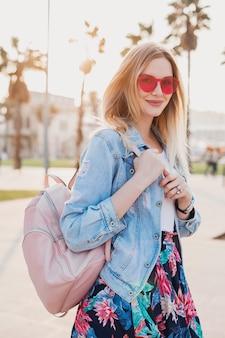 Довольно улыбающаяся женщина гуляет по городской улице в стильной юбке с принтом и джинсовой куртке oversize, в розовых солнцезащитных очках, с кожаным рюкзаком, тренд летнего стиля