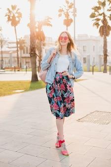 ピンクのサングラスを身に着けているスタイリッシュなプリントスカートとデニムの特大ジャケットで街の通りを歩いてかなり笑顔の女性、夏のスタイルのトレンド