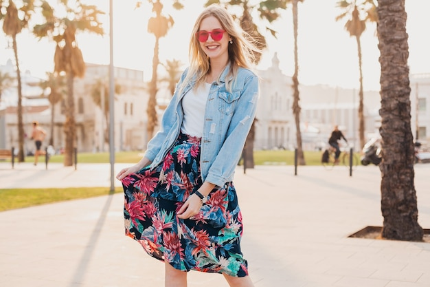 Довольно улыбающаяся женщина гуляет по городской улице в стильной юбке с принтом и джинсовой куртке oversize в розовых солнцезащитных очках, летний тренд
