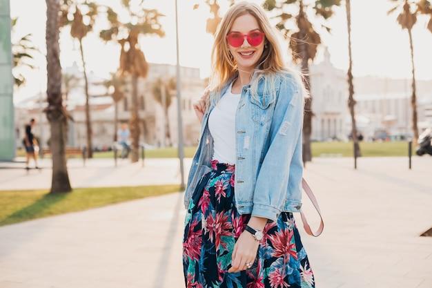 핑크 선글라스를 착용하는 세련된 프린트 스커트와 데님 특대 재킷, 여름 스타일 트렌드의 도시 거리에서 걷는 예쁜 웃는 여자