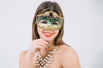 Pretty smiling woman wearing green decorative carnival mask