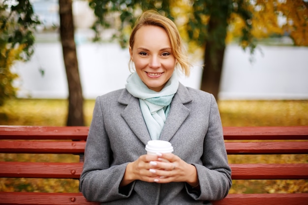 Pretty smiling woman with blonde hair holding cup of drink looking at camera sitting on a bench
