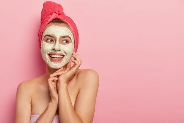 Pretty smiling woman with clay mask, makes beauty step, cleans face, wears wrapped towel on head, stands shirtless, gets pleasure, reduces pimples, copy space area against pink wall