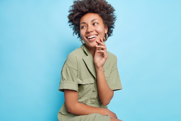Pretty smiling woman with curly afro hair looks away smiles broadly shows perfect white teeth wears stylish dress concentrated on left isolated over blue wall