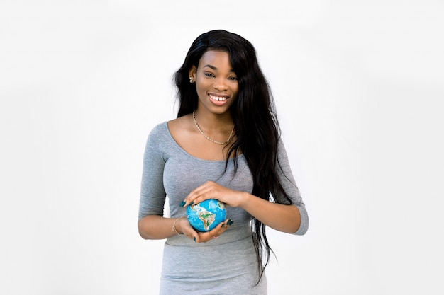 Pretty smiling young african american woman in casual wear holding the little earth globe in hands