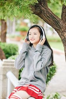 ヘッドフォンで音楽を聴いてかなり笑顔の若いアジアの女子高生