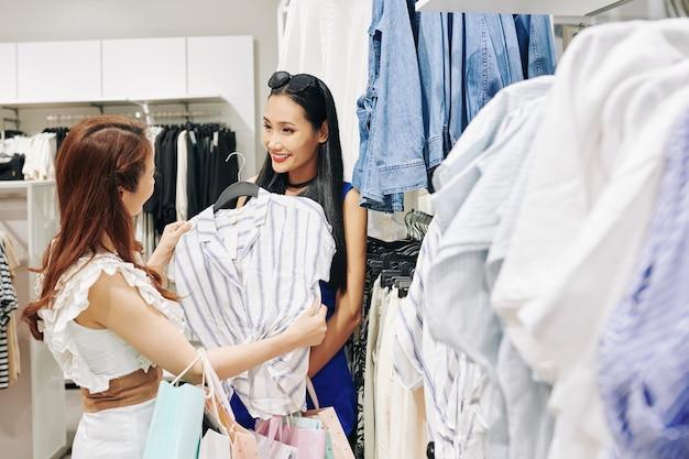 백화점에서 옷을 사는 꽤 웃는 젊은 아시아 여성