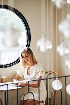 Довольно улыбающаяся молодая блондинка женщина сидит за столом в кафе и пишет в планировщике свои творческие идеи
