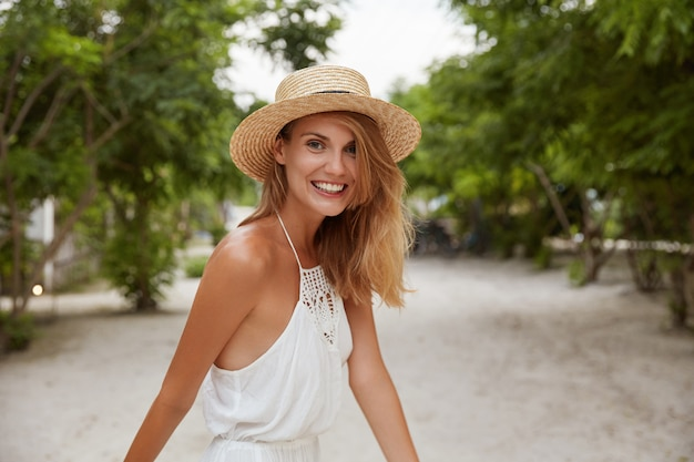 Pretty smiling young female with glad expression, wears fashionable white dress and hat, strolls outdoor, has tanned healthy skin, enjoys summer vacations.