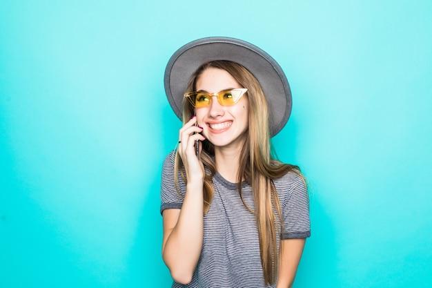 緑の背景に分離された電話でファッションtシャツ、帽子、透明ガラスのかなり笑顔の若いモデル協議