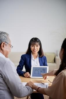 かなり笑顔の若い不動産業者が、年配のカップルに建築計画のあるタブレットコンピューターを見せています...