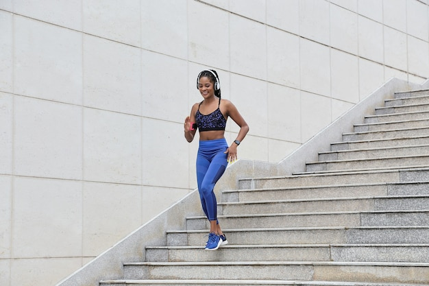 Довольно улыбающаяся молодая спортсменка спускается по лестнице во время подготовки к марафону