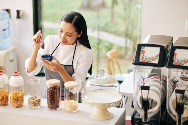 뿌리와 작은 그릇에 아이스크림을 장식 꽤 웃는 젊은 베트남 여자