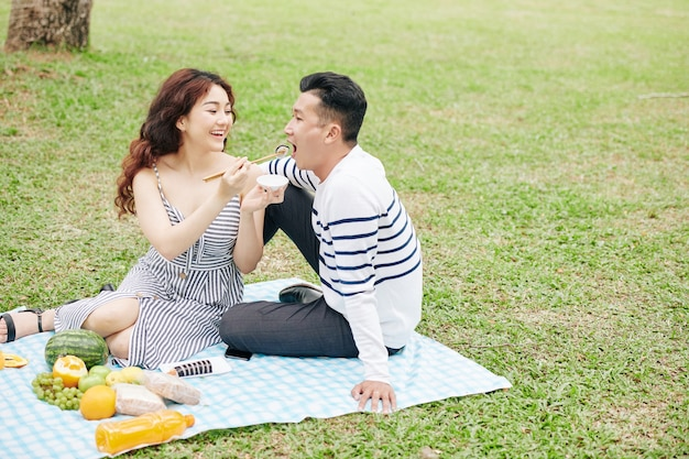 Pretty smiling young vietnamese woman feeding boyfriend with delicious suchi when having picninc in park