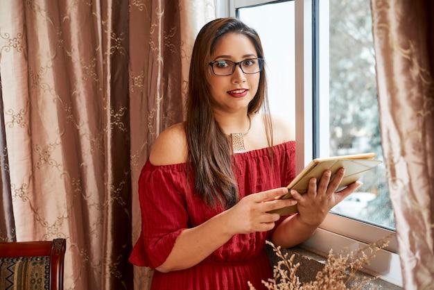 窓際に立っているデジタルテーブルでかなり笑顔の若い女性、彼女はコロナウイルスのパンデミックのために自宅で働いています