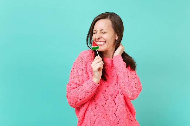 青い壁の背景、スタジオの肖像画に分離されたスイカのロリポップを手に持って目を閉じてニットピンクのセーターでかなり笑顔の若い女性。人々のライフスタイルの概念。コピースペースをモックアップします。
