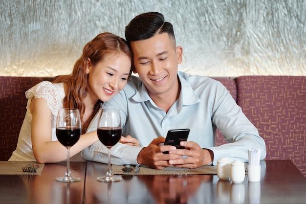 彼氏の肩に寄りかかって、レストランで食べ物を待っているときにスマートフォンで面白いビデオを見ているかなり笑顔の若い女性