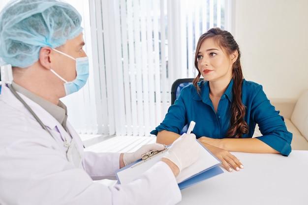 의료 마스크와 고무 장갑에 의사의 권장 사항을 듣고 꽤 웃는 젊은 여자