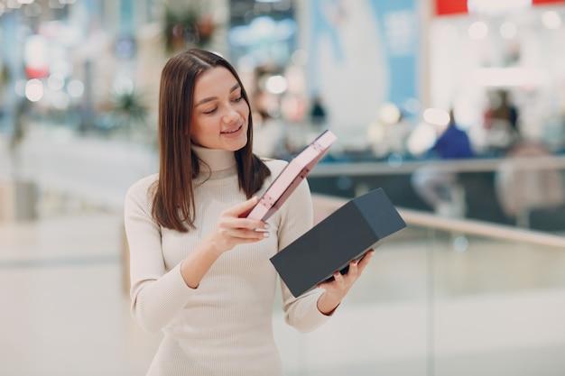 분홍색 선물 상자를 열고 쇼핑몰에서 놀라고 꽤 웃는 젊은 여자. 크리스마스, 공휴일, 발렌타인 데이 컨셉
