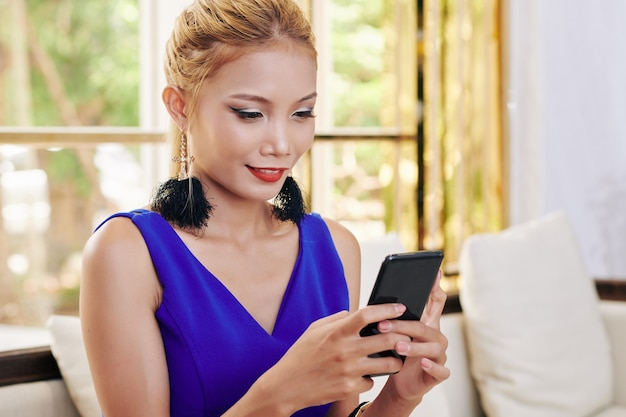 Pretty smiling young woman reading text messages from her friends on smartphone