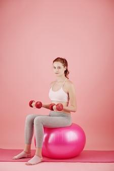 Довольно улыбается молодая женщина, сидящая на фитнес-мяч с гантелями в руках