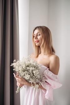 꽃다발을 들고 서 있는 꽤 웃는 젊은 여성