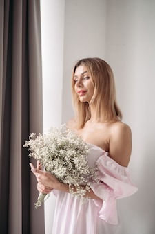 Giovane donna abbastanza sorridente in piedi con un mazzo di fiori