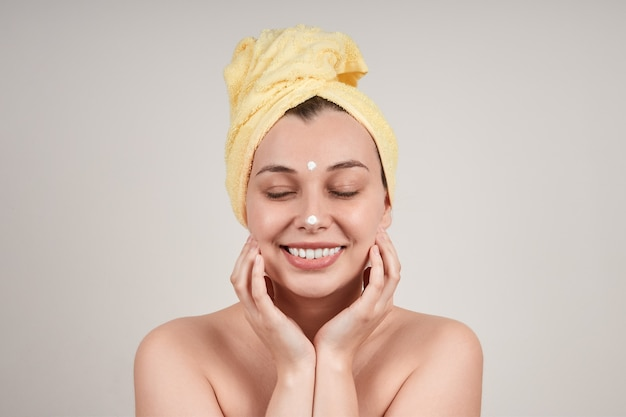 裸の肩、頭に黄色いタオル、顔にクリームを塗り、目を閉じて、かなり笑顔の若い女性。灰色の壁に隔離します。