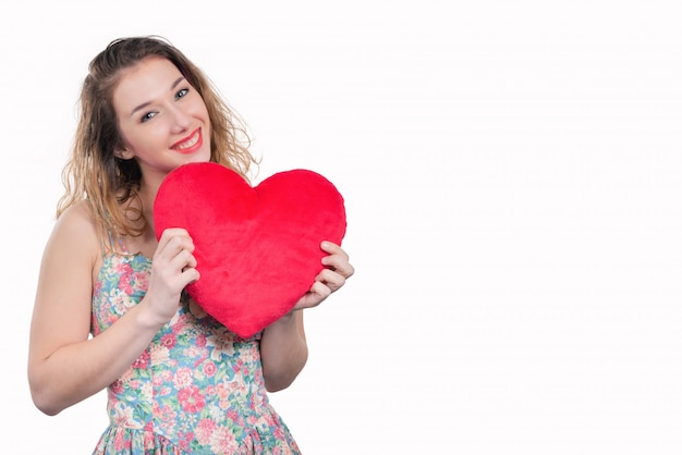 Pretty smiling young woman with a red heart on white