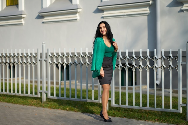 Pretty smilling brunette girl wearing gray skirt, green sweater and stylish green jacket posing at camera