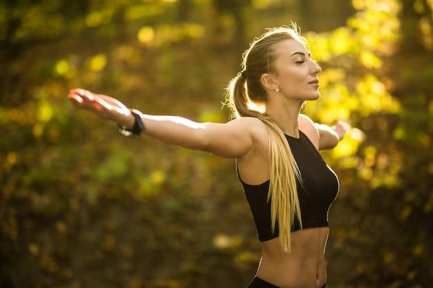 Красивая спортивная женщина делает упражнения йоги в парке