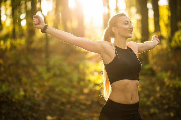 Bella donna sportiva che fa esercizi di yoga nel parco