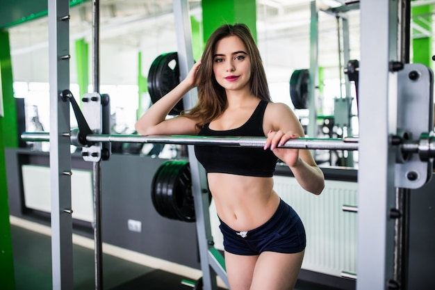 Pretty sportive strong young woman doing exercises with barbell dressed up in fashion sportswear in sportclub