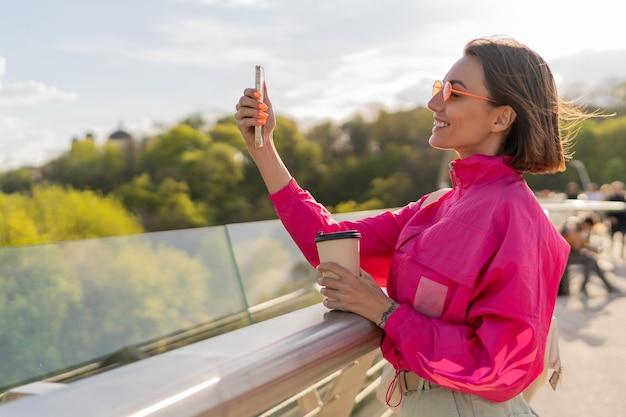 Donna abbastanza sportiva in giacca rosa brillante che cammina presto marning all'aperto