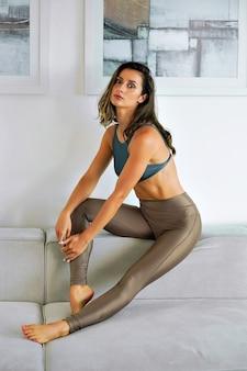 Pretty sportive woman, posing on beige sofa