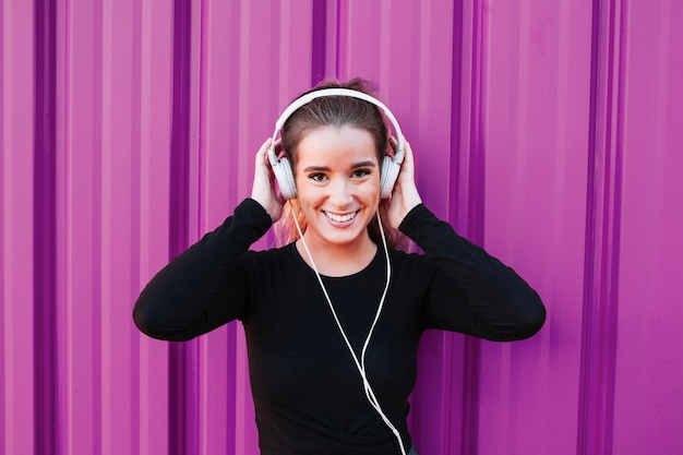 Pretty sportswoman in headphones smiling at camera