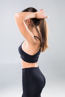 Pretty sportswoman holding up her ponytail isolated over white wall
