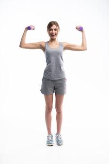 Довольно спортивный девушка держит гантели веса и делает упражнения на белом.