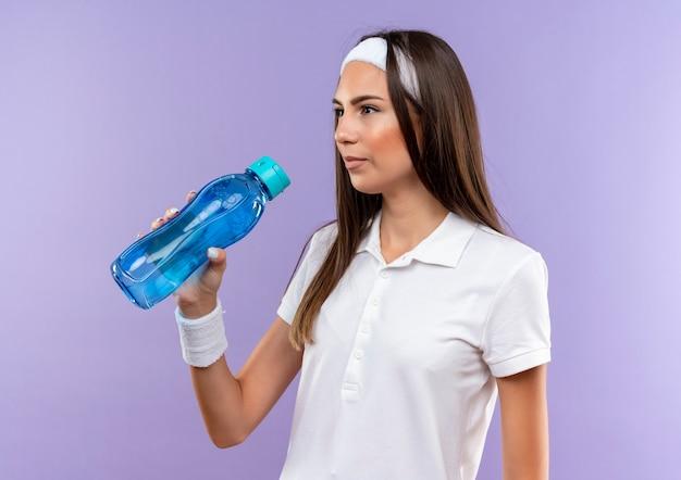 Довольно спортивная девушка с ободком и браслетом держит бутылку с водой, глядя на сторону, изолированную на фиолетовом пространстве